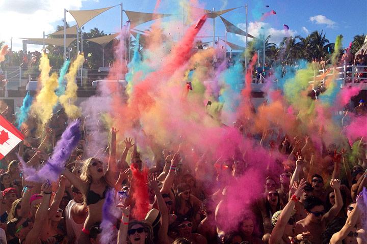Gente con bombas de colores en The Oasis Beach club en Hotel Oasis Cancun Lite