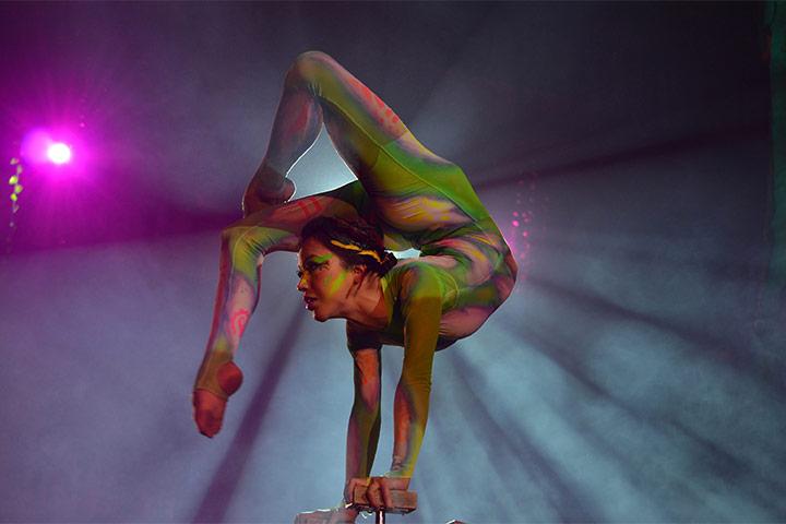 Acróbata haciendo contorsionismo con traje de colores luminosos para show Origen en Locación Red Circus en Hotel The Pyramid at Grand Oasis