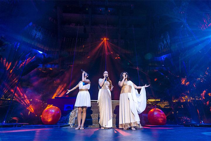 Tres mujeres cantando con vestidos blancos para show Armonía en Locación Red Circus en Hotel The Pyramid at Grand Oasis