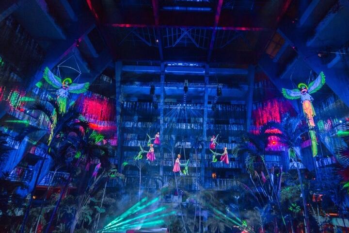 Show Quetzal con bailarines vestidos con colores luminosos visto desde las mesas en Locación Red Circus en Hotel The Pyramid at Grand Oasis