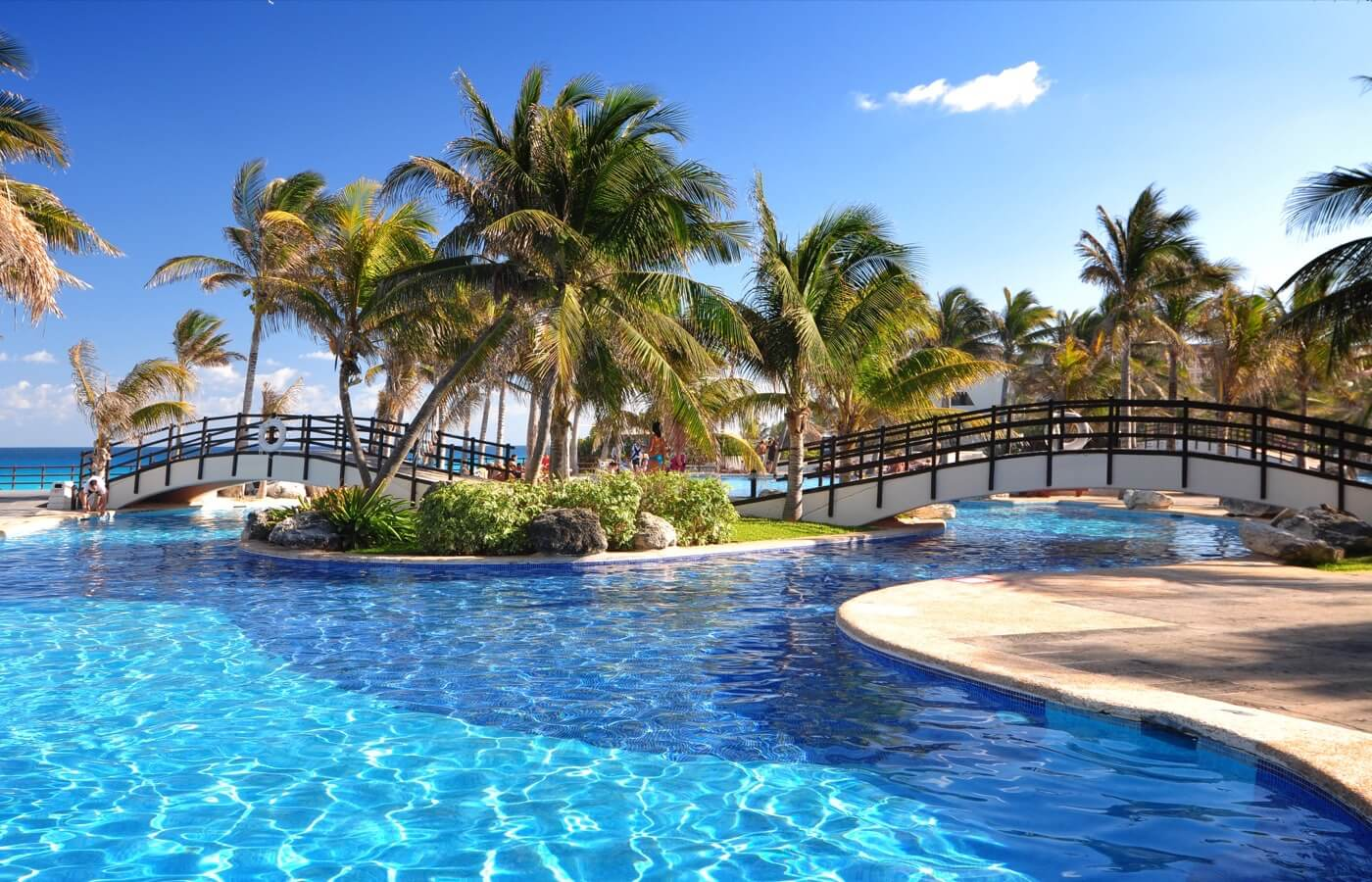 Swimming pools overlooking the bridge with palm trees at Hotel Grand Oasis Cancun