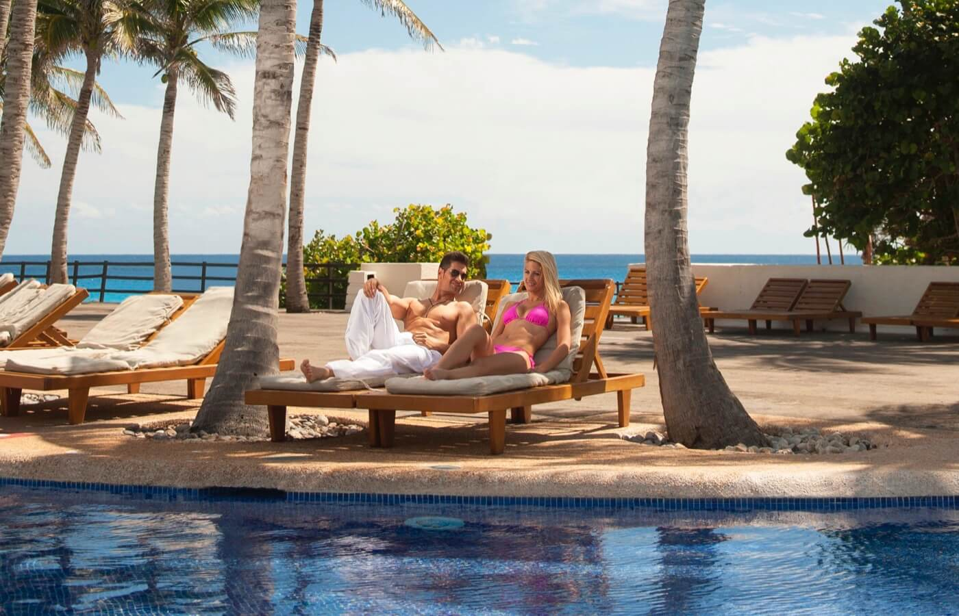 Albercas junto a un restaurante con palmeras en el Hotel Grand Oasis Cancun