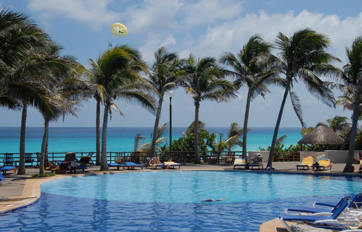 Swimming pools next to a palm tree restaurant at the Grand Oasis Cancun Hotel