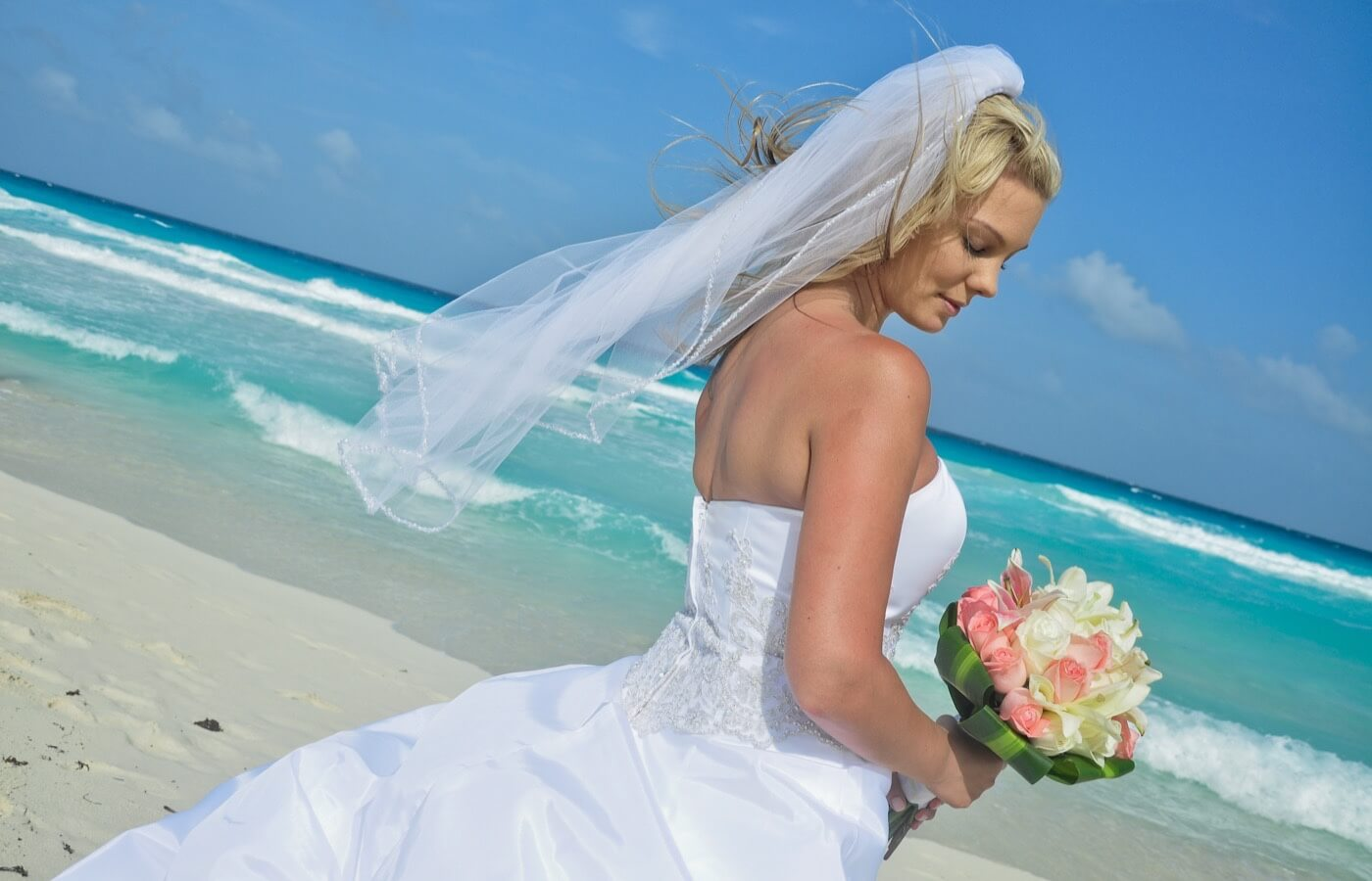 Woman in a wedding gown in a beach photo shoot with bouquet of white roses and roses at the Grand Oasis Cancun Hotel