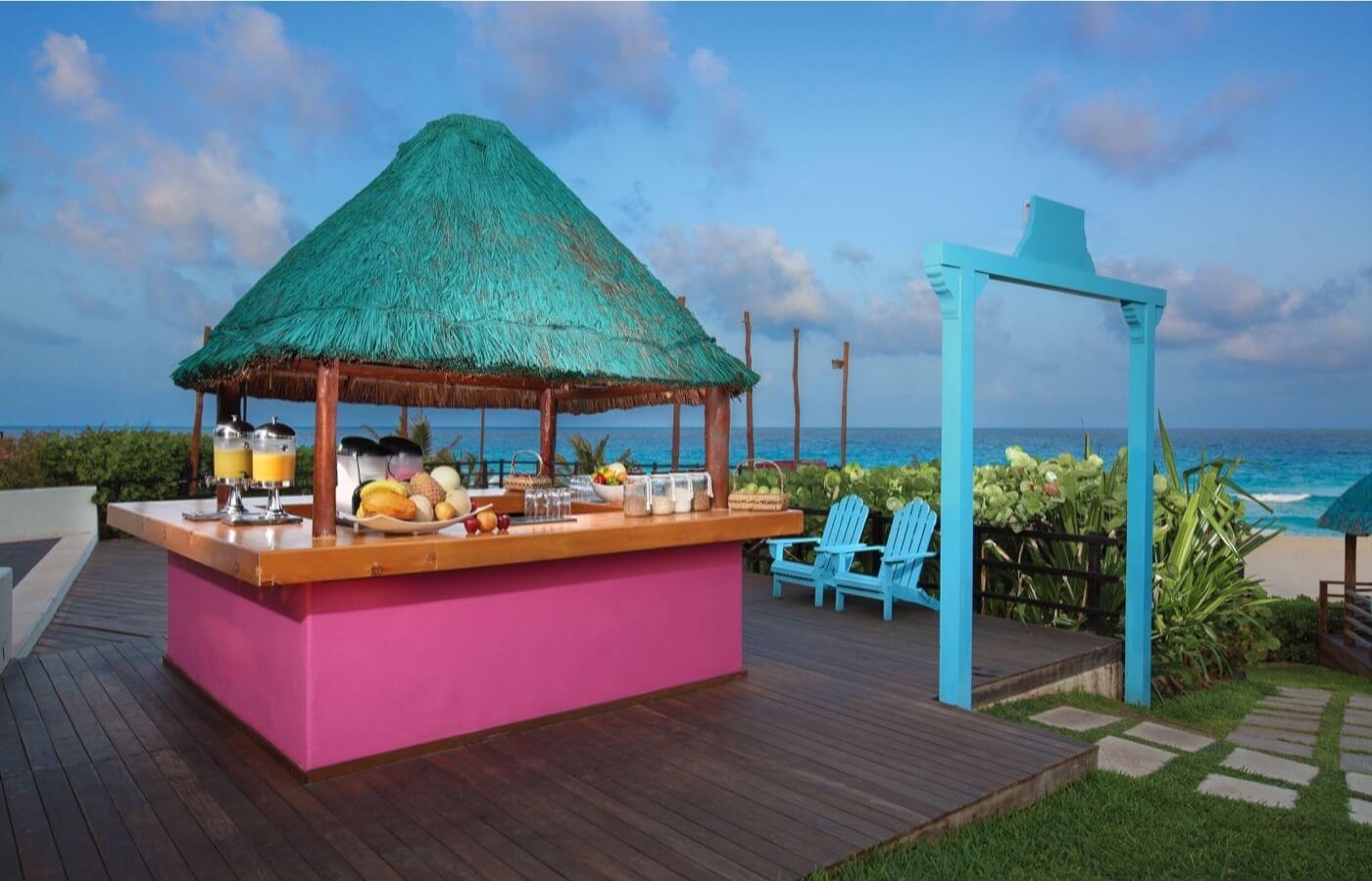 Mujer disfrutando de bebida tipo coctel en bar de alberca en Hotel Grand Oasis Cancun