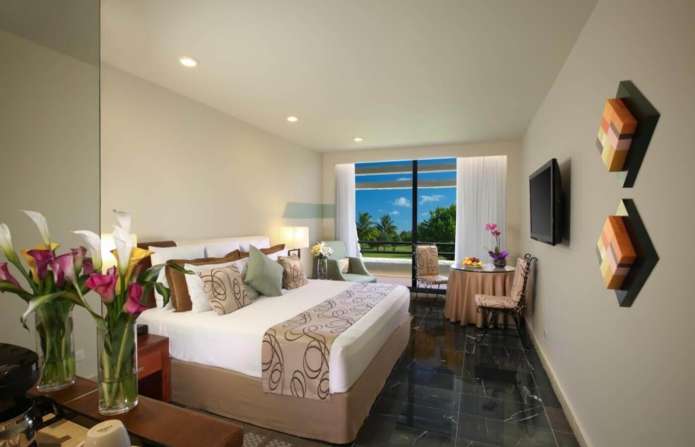 Habitación Vista al Mar vista lateral con decoración café, cama King Size y hermosa vista en hotel Grand Oasis Cancun