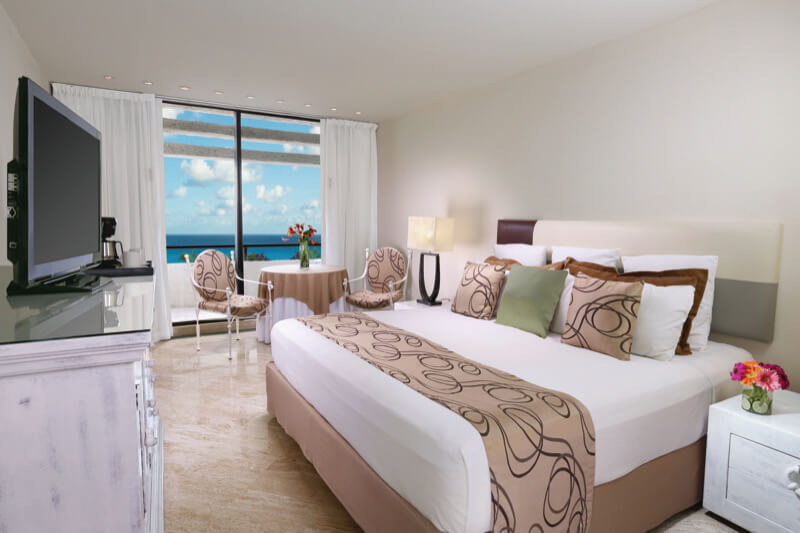 Ocean View room in light colors with King Size bed and beautiful view in Grand Oasis Cancun hotel.