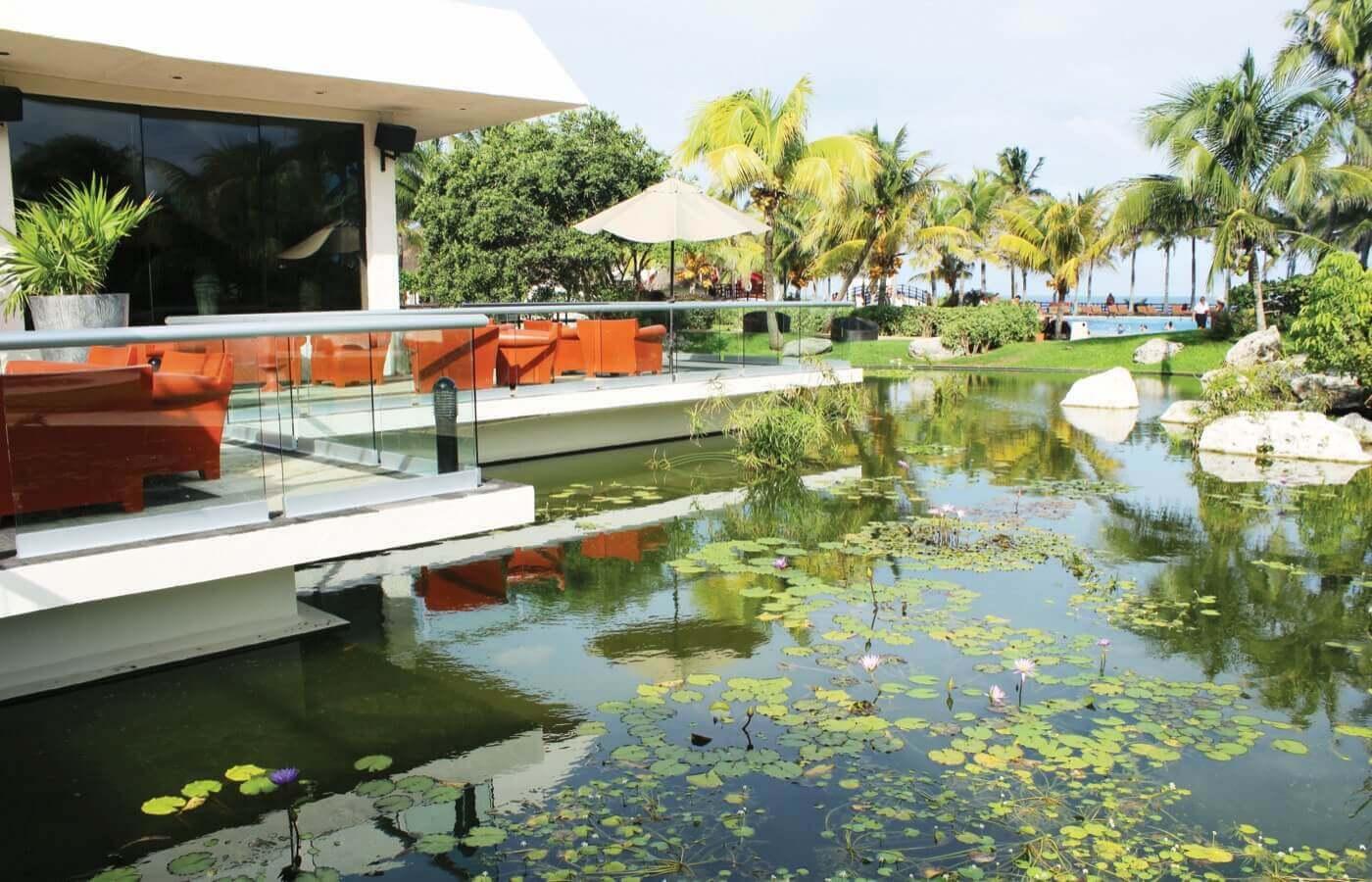 Terraza con sillones junto a lago en hotel The Pyramid at Grand Oasis