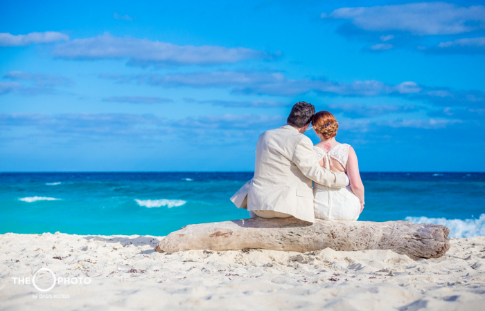 Married couple with their backs to the beach wedding photo shoot