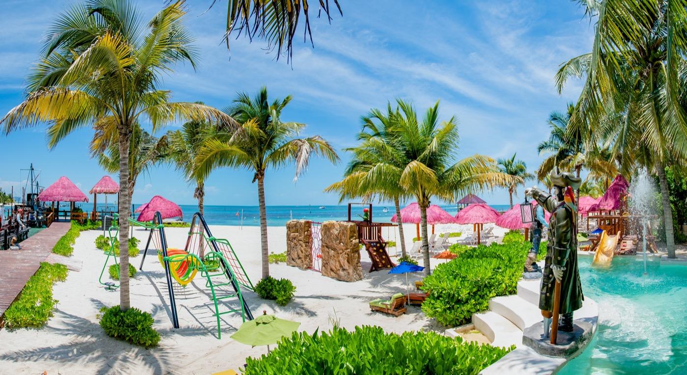 Camastros bajo palmeras en la playa en Hotel Grand Oasis Palm