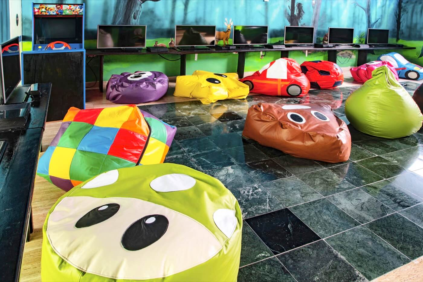 Playground at KiddoZone with consoles and puff armchairs at Hotel Oasis Palm