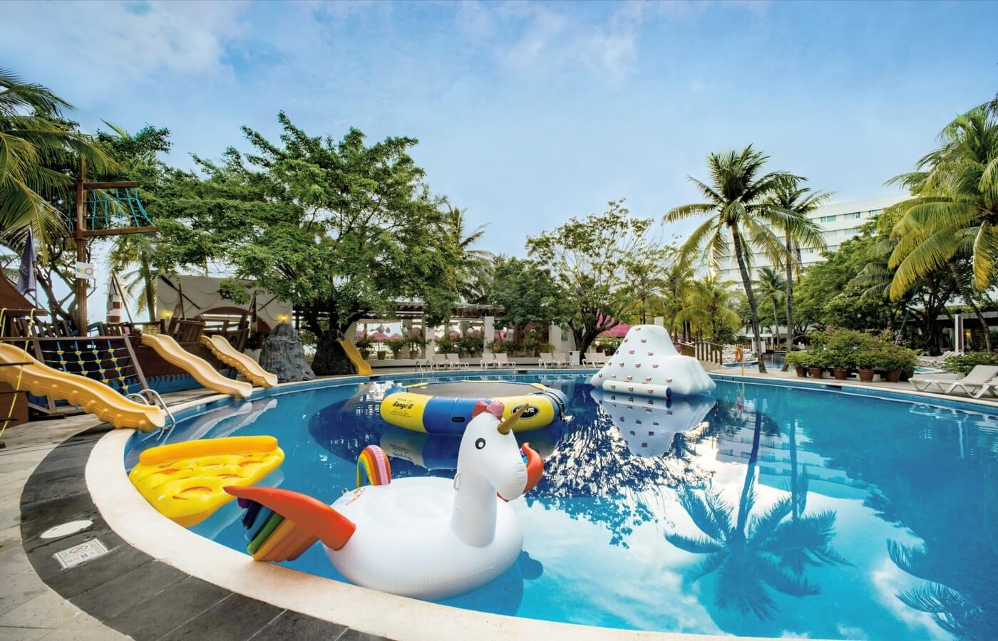 Niño jugando con el agua en alberca de KiddoZone en Hotel Oasis Palm