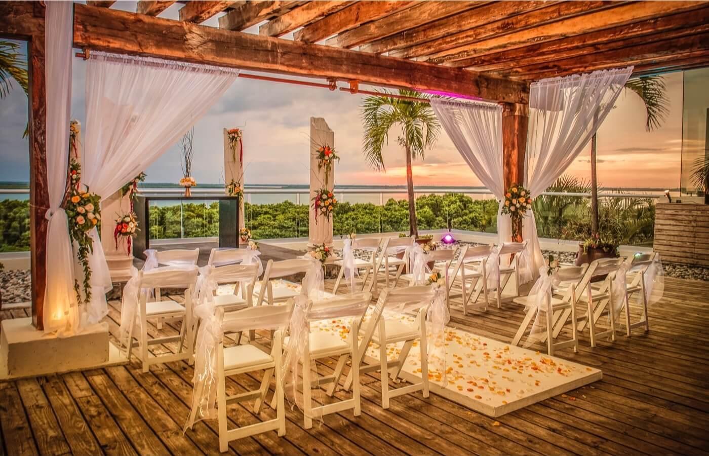 Camino de pétalos de flores para entrada de novia en ceremonia de bodas al aire libre junto al mar