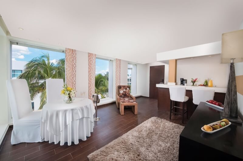Sala en Master Suite con sillones, mesa, sillas y mini bar en hotel The Sian Ka'an at Grand Tulum