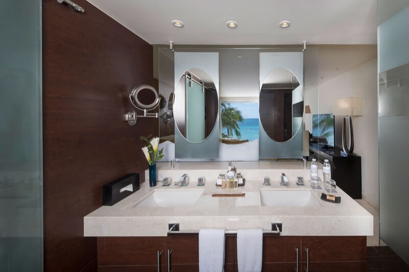 Baño de Habitación Sian Ka'an con vista al oceano con lavamanos doble, espejo grande y amenidades en hotel The Sian Ka'an at Grand Tulum