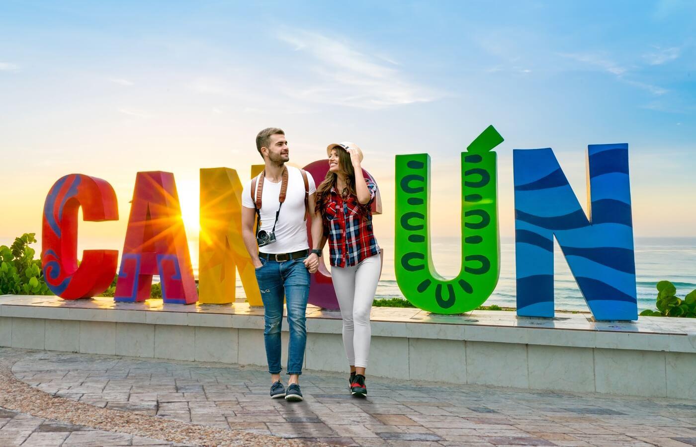 Pareja de turistas frente a letras gigantes de Cancún