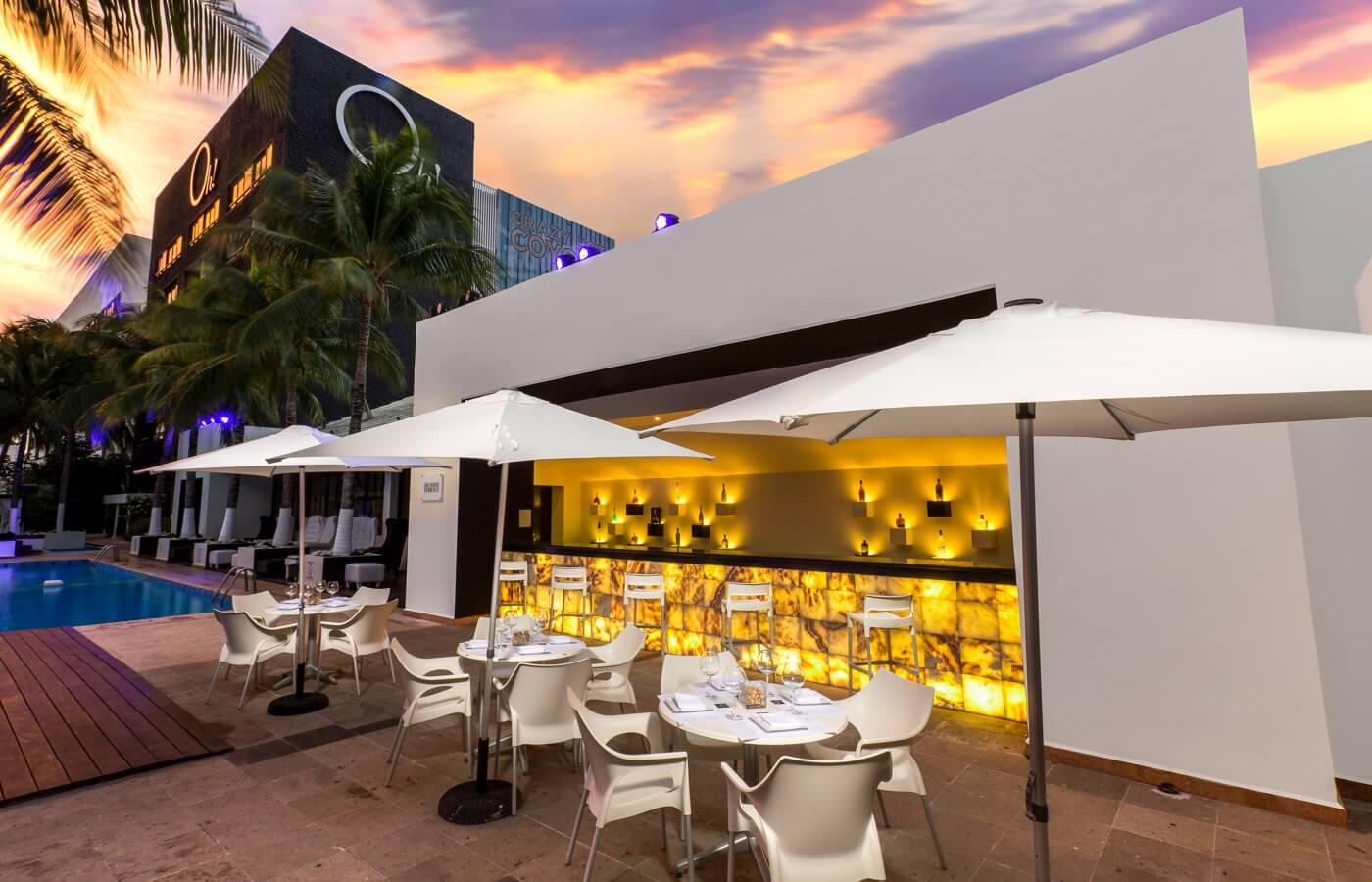 Área de Albercas y Restaurante The White Terrace visto de noche en Hotel Oh! Cancun The Urban Oasis