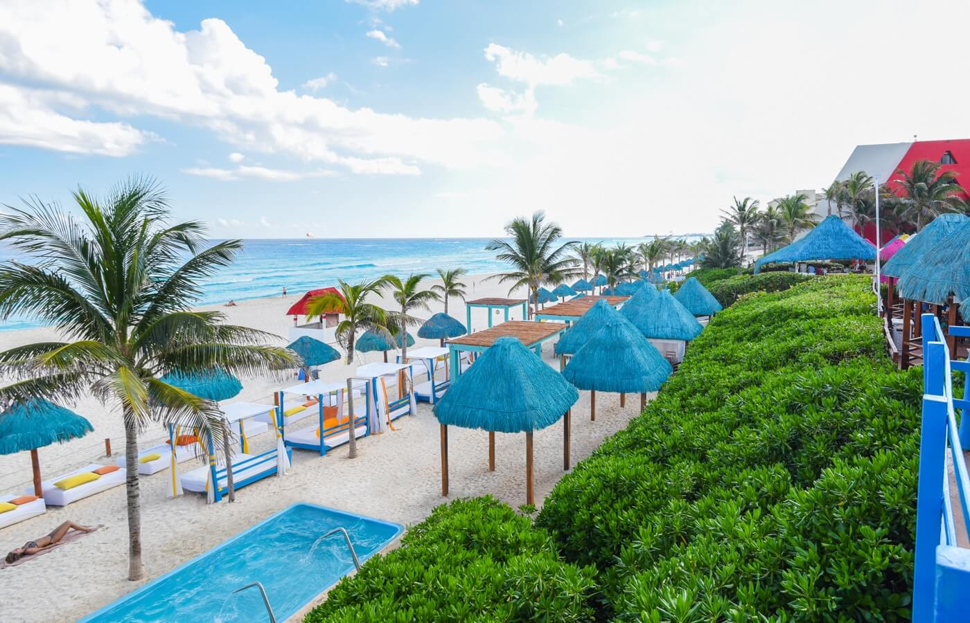 View to the beach with beds and palapas in Oasis hotels
