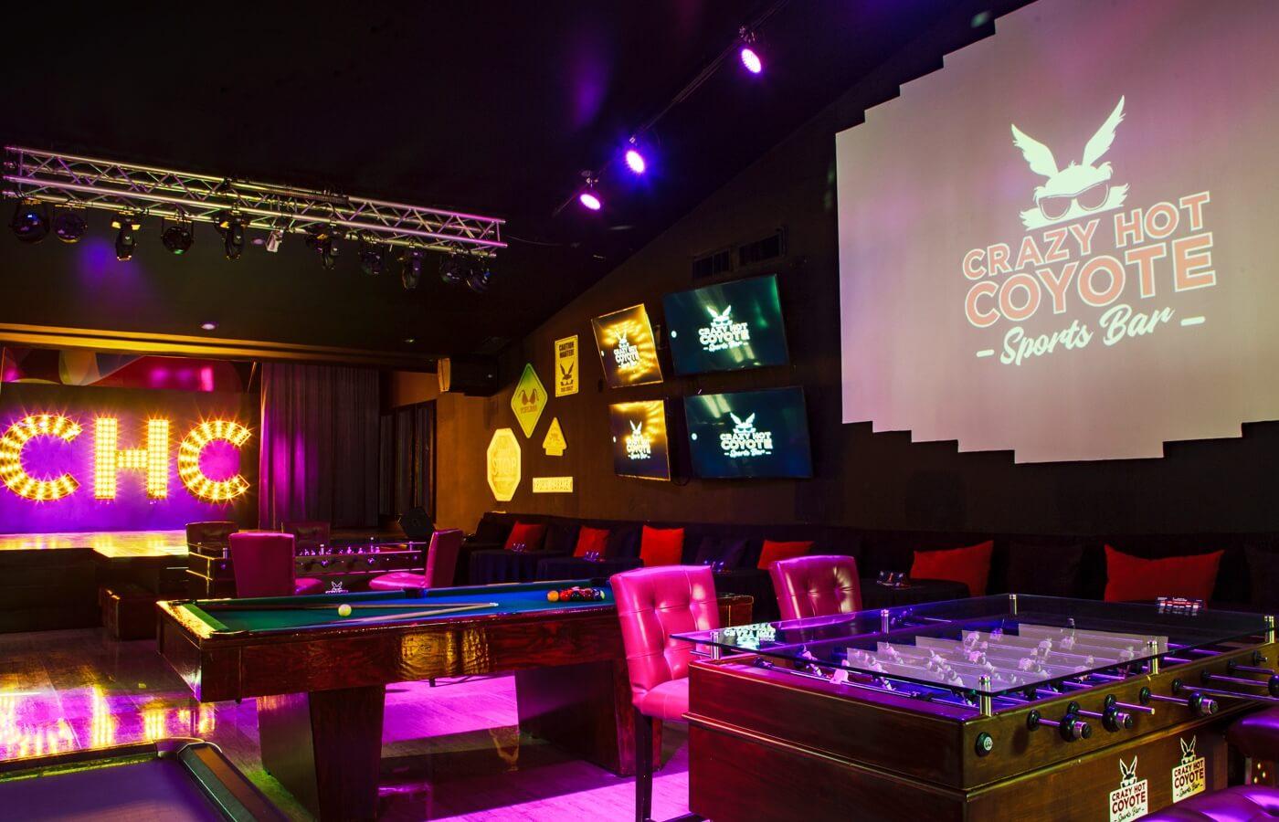 Vista interior de Crazy Hot Coyote Sports Bar con luces y mesas de juego