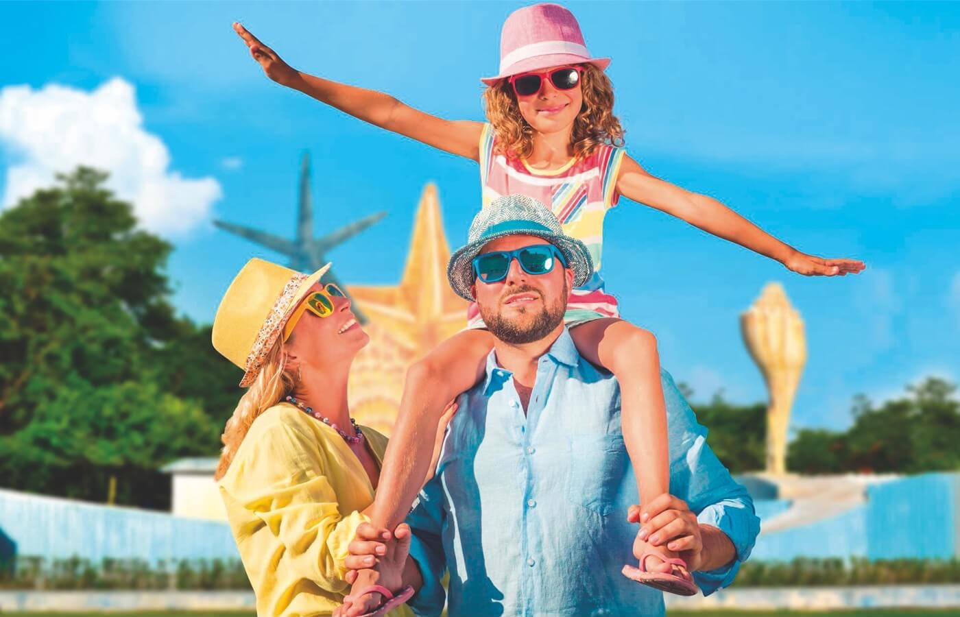 """Parents with daughter on their shoulders in front of the Fantasía Caribeña monument, """"El Ceviche""""."""
