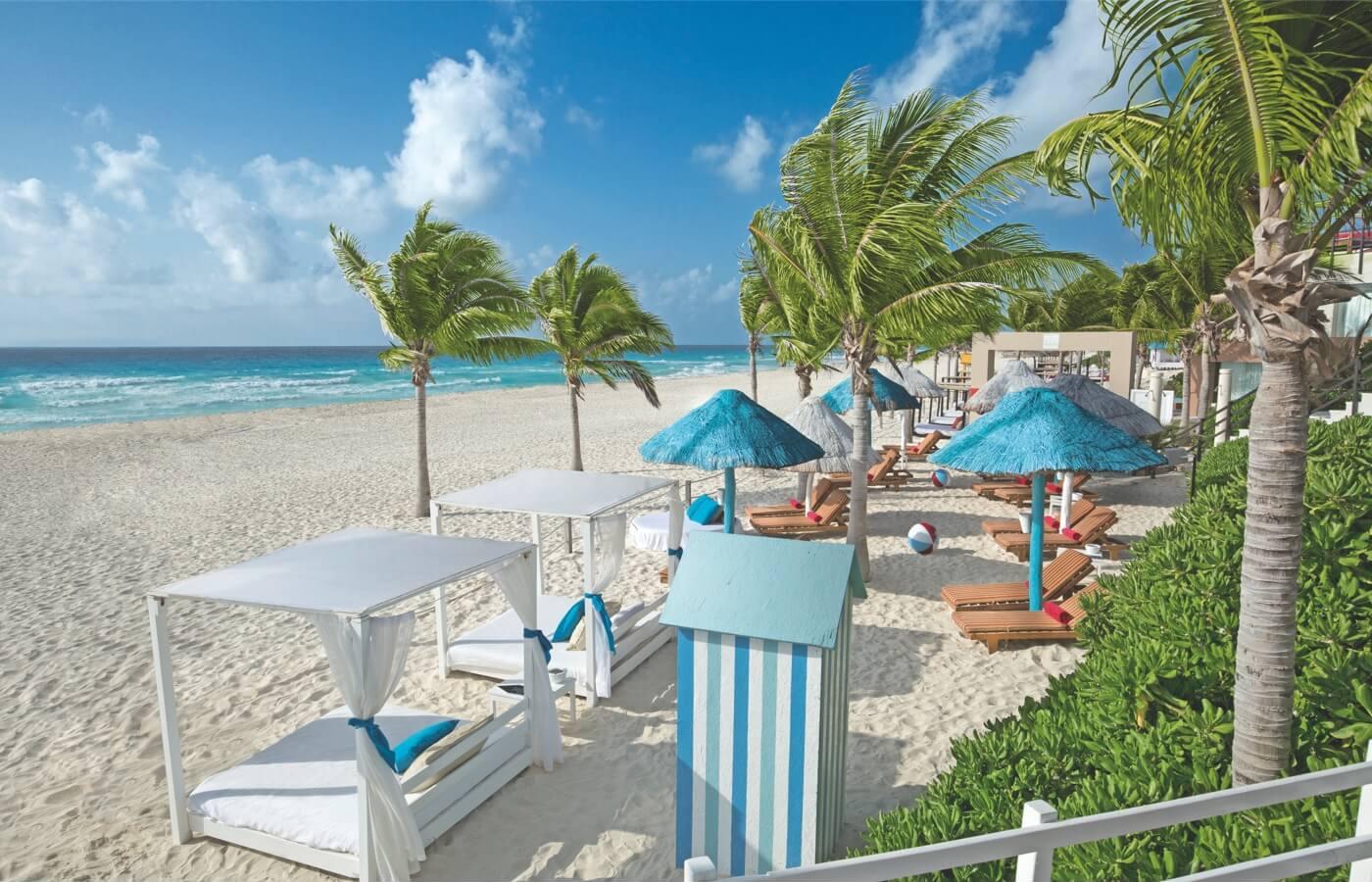 Vista a la playa con Camastros y palapas de hoteles Oasis