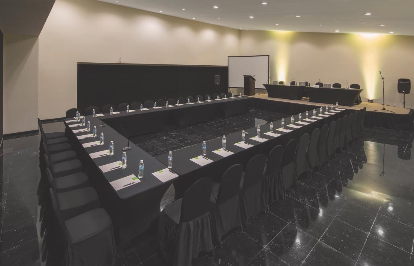 Sala para reuniones con sillas, mesas y escenario en Smart Cancun by Oasis